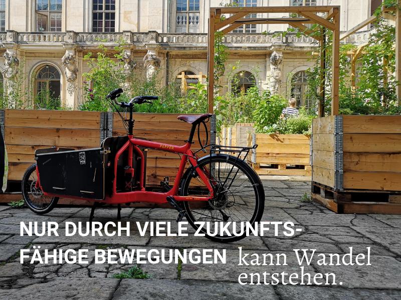 Nur durch zukunftsfähige Bewegungen kann Wandel entstehen. Rotes Lastenrad vor Hochbeeten in der Stadt